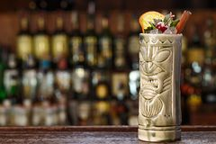 Exotic cocktail on the bar in tiki glass. Exotic cocktail Rio Punch on the bar with a place to write a recipe. The cocktail is decorated with orange, cinnamon Royalty Free Stock Image