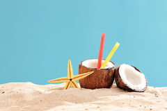 Exotic cocktail in a coconut shell on a sandy surface Royalty Free Stock Photography