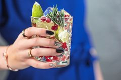 The exotic cocktail and female hands. The female hands and exotic cocktail at studio Royalty Free Stock Photos