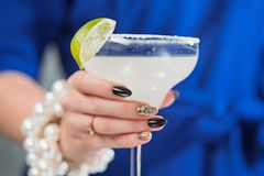 The exotic cocktail and female hands. The female hands and exotic cocktail at studio Stock Photography