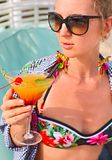 Exotic cocktail glass in womans hand. On poolside royalty free stock image