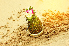 Exotic cocktail in a pineapple on a beach Stock Image