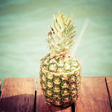 Exotic cocktail in the pineapple. Sea pier. Concept of luxury va Stock Photo