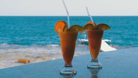 Exotic Cocktails on the Bar Counter on the Background of the Red Sea. Glass with Tropical Long drink with Fresh Red strawberry mousse and freshly squeezed stock video footage