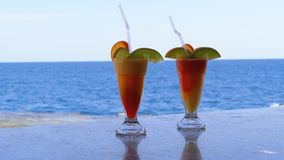 Exotic cocktails on the bar counter on the background of the red sea. Glass with tropical long drink with fresh red strawberry mousse and freshly squeezed stock video