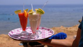 Exotic Cocktails in a Glass with a Straw on a Tray on the Background of the Sea. Egypt. stock video