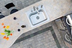 Exotic concrete counter top in an outdoor kitchen. Exotic concrete counter top and sink in an outdoor kitchen set with two glasses and a bottle of red wine and a Stock Photos