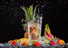Exotic drink with splash on black background Royalty Free Stock Photos