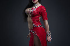Exotic eastern women performs belly dance in ethnic red dress. Young beautiful exotic eastern woman performs belly dance in ethnic red dress on gray background Stock Images