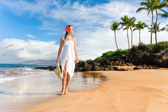Exotic elegant tropical woman beach. Elegant woman walking along tropical scenic beach with palm trees, white sarong, and hat smiling Royalty Free Stock Images