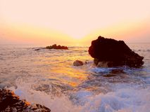 Exotic evenig sunset, turkey beach. Bright colorful sunset on the sea on a wild beach, stones boulders of red-brown color, glare of water, waves, sea spray Royalty Free Stock Photos