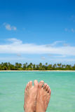 Exotic feet. Feet abowe water, with an exotic beach with palms in the background. Taken at the Dominican Republic Stock Images