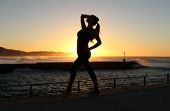 Exotic female dance silhouetted. A sexy young exotic dancer is dancing on the pier and the rising sun over the ocean creates a beautiful silhouette Stock Images