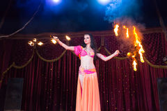 Exotic Fire Dancer Twirling Flaming Batons. Exotic Dark Haired Fire Dancer Twirling Flaming Baton Apparatus on Stage Lit by Bright Spotlights Royalty Free Stock Image