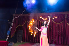 Exotic Fire Dancer Twirling Flaming Batons. Full Length of Exotic Dark Haired Fire Dancer Wearing Bright Costume and Twirling Flaming Baton Apparatus on Stage Royalty Free Stock Image