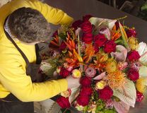 In exotic flower shop florist finishing bouquet Royalty Free Stock Images