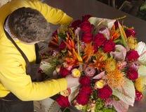 In exotic flower shop florist finishing bouquet