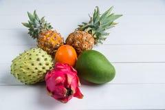 Exotic fresh summer fruits on white background. Dragon fruit, pineapple, persimmon, mango, annona cherimola flat lay royalty free stock photo