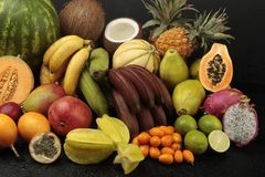 Exotic fruit arrangement. On black background with waterdrops Stock Image
