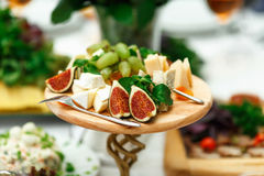 Exotic fruits and cheese lie cut on a wooden tray Stock Photography
