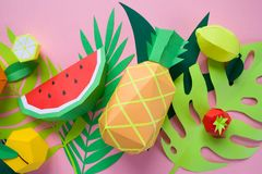 Exotic fruits made of paper. Handmade paper art. Exotic fruits with different tropical leaves made of paper on pink background royalty free stock photos