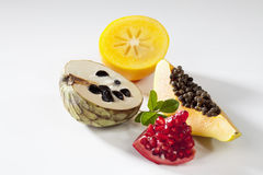 Exotic fruits, papaya, pomegranate, cherimoya, kaki slices on white background Royalty Free Stock Photography