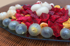 Exotic fruits salad with Dragon Fruit, pitahaya,litchi, mangosteen, banana and rambutan on blue glass plate. Shallow DOF photo of exotic fruit salad with Dragon Stock Images