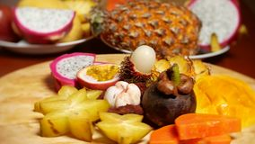 Exotic fruits on the table. 4k, carambola and dragon fruit, papaya, mango, mangosteen and longan, passion fruit, fruit. Cut into pieces, rotate on a cutting stock footage