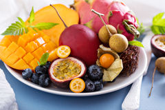 Exotic fruits on white plate. Variety of exotic fruits on white plate stock photo
