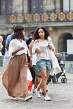 Exotic girls on the Amsterdam Dam Square. AMSTERDAM-AUG. 19, 2012. Two exotic looking girls walking on the Dam Square on Aug. 19 in Amsterdam. 177 different Stock Photo
