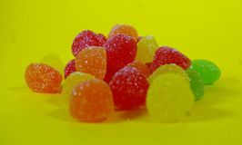 A bunch of gummies sweet on a yellow background. Exotic honduras fuit called guayaba or guaba color green with a yellow background Stock Images