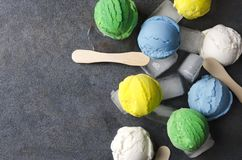 Exotic kinds of ice cream with ice cubes on gray table,top view.Unusual types of ice cream balls Closeup of various ice cream flav stock image
