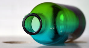 Exotic lime green and cobalt blue bottle. Green and blue glass bottle empty, sidelit on whte base with white background Stock Images