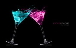 Exotic Liquors. Stemmed Cocktail Glasses Making A Toast Splashing Out. Royalty Free Stock Images