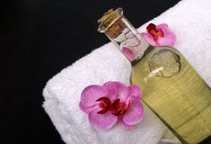 Exotic Massage oil. Bottle of massage oil on bath towel with pretty pink orchid blossom decoration Royalty Free Stock Photo