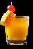 Exotic orange cocktail on black. Tumbler of exotic tropical orange cocktail chilled with ice and garnished with decorative orange peel an a maraschino cherry on stock photo