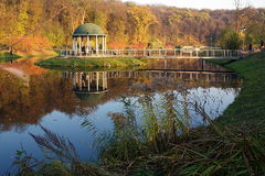 Exotic Panorama view on lake with reflex in water  of little hou. Exotic Panorama view on exotic park with lake and red yellow green color  trees, and  reflex in Royalty Free Stock Images