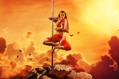 Exotic pole dancing woman. Young woman exotic style pole dancing with snake on mountain top. Asian style and red warm colors. Tattoo on hand Stock Photo