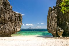 Beach between tall rocks. Exotic pristine white sandy beach with clear blue water Royalty Free Stock Photo