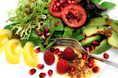 Exotic Salad. Salad on a white plate  with red roma and yellow heirloom tomatoes, avocado slices, spinach leaf, pomegranate seeds, Raspberries topped with Olive Royalty Free Stock Photos