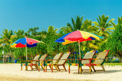 Exotic sandy beach with sun umbrellas and chairs Stock Image