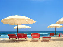 Exotic scene with parasols. And red chairs near the ocea Stock Images