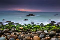 Nature Seascape with Rocks Covered by Green Mosses, Blurred Waves and Dark Cloudy Sky stock image