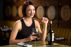 Exotic sexy beautiful woman on a dinner date at winery barrels enjoying evening night out Stock Photos