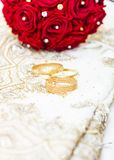 Exotic silk asian wedding dress and gold bracelets engraved with diamonds. And red roses bouquet with pearls and diamonds stock images