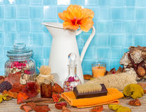 Exotic spa bathing accessories. With an orange hibiscus flower in a jug against turquoise blue tiles with rose petal potpourri , bath salts, sponges and a Royalty Free Stock Photos
