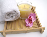 Exotic Spa Pampering. With towel, cream scented relaxing candel and orchid pretty blossoms Royalty Free Stock Photos