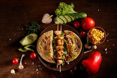 Exotic still slife with pita, fresh vegetables and kebab over wooden background, selective focus. royalty free stock photography