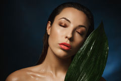 Exotic style. Fashion photography. Naked woman leaning to green plant. Royalty Free Stock Photos