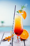 Exotic Tequila Sunrise cocktail. Colourful exotic Tequila Sunrise cocktail served on the rocks with crushed ice and a swizzle spoon Royalty Free Stock Photography